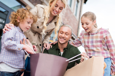 Kaukasische familie op zoek naar boodschappentas op straat