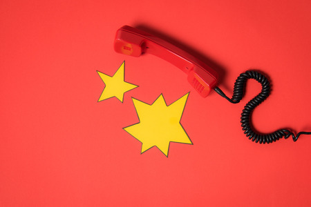 Traditional telephone receiver and blank star shaped speech bubbles isolated on red