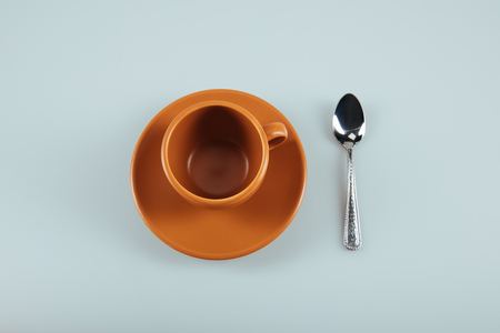 empty ceramic coffee cup on saucer with silver teaspoon isolated on grey