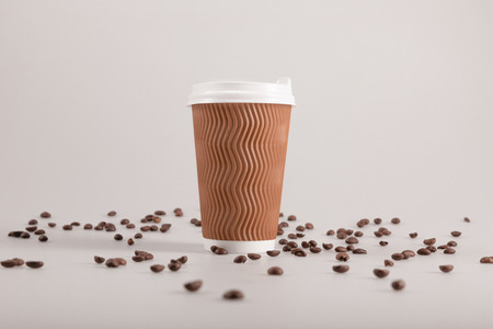 disposable coffee cup with scattered coffee grains isolated on beige