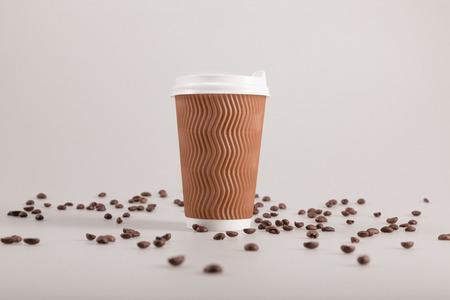 Tazza di caffè usa e getta con chicchi di caffè sparsi isolato su beige Archivio Fotografico - 83879409