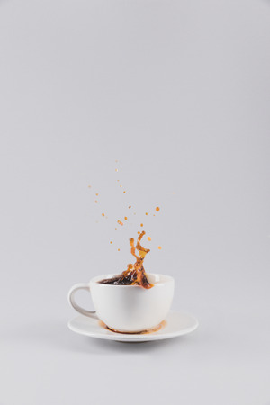 coffee splashing out of white cup on saucer, isolated on grey with copy space