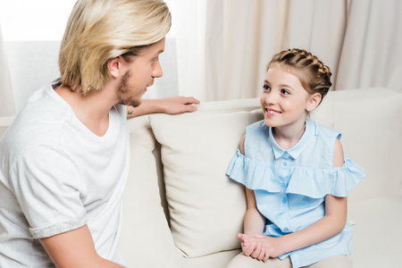 father and daughter looking at each other and talking while sitting on sofa at home
