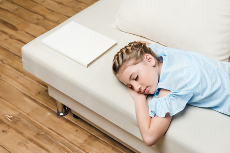 白い本とソファに眠っている愛らしい少女 写真素材