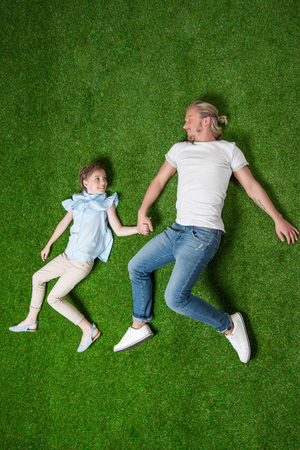 father with little daughter holding hands while lying on the grass