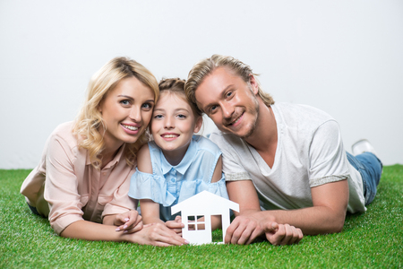 happy family lying on the grass and holding paper cut of house