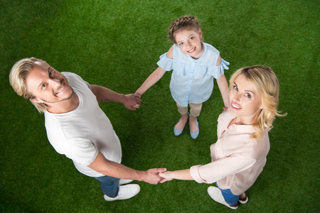 family looking at camera while standing in circle and holding hands Stock Photo