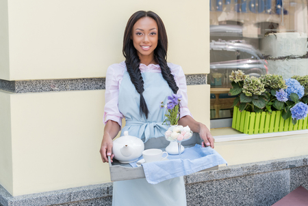 young waitress in apron holding tray with tea set in outdoor cafe Stok Fotoğraf