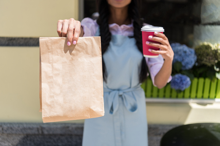 waitress holding paper bag and disposable cup