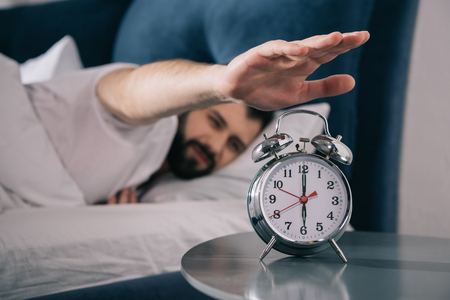 young man trying to turn off alarm clock while lying in bed at morning