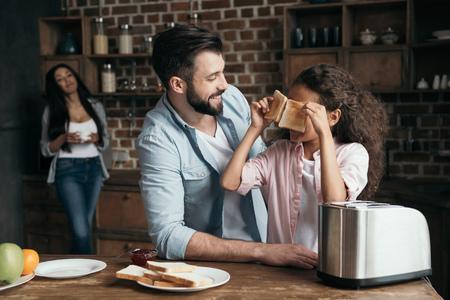 bebaarde man kijken naar schattige kleine meisje houdt van toast in de keuken Stockfoto