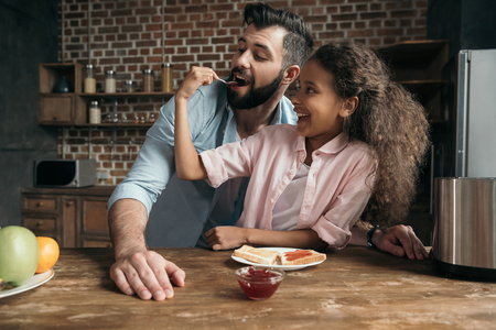 girl feeding father with sweet jam from teaspoon
