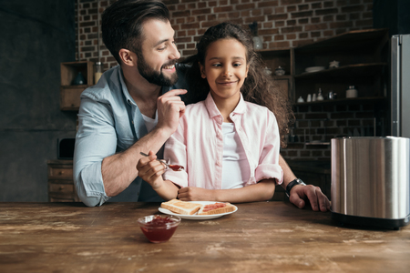 girl having fun while preparing toasts with jam together with father Stock fotó
