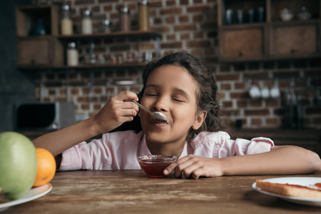 little girl with eyes closed eating sweet jam from teaspoon