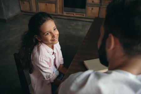 테이블에 앉아있는 동안 아버지와 이야기 사전 사춘기 소녀