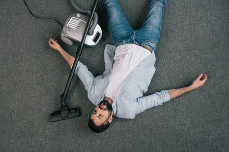 young man lying near vacuum cleaner on the floor at home Stok Fotoğraf