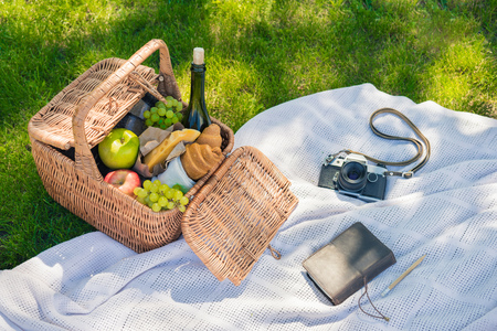 Wicker picnic basket with fruits and wine, vintage camera and notebook with pencil