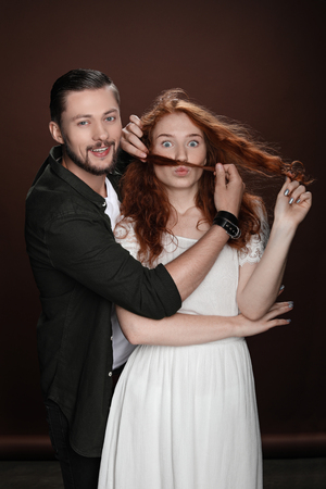 Young cheerful couple, man making mustache of hair for his girlfriend