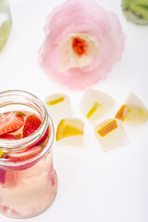 close up view of healthy drink with strawberries and citrus ice cubes