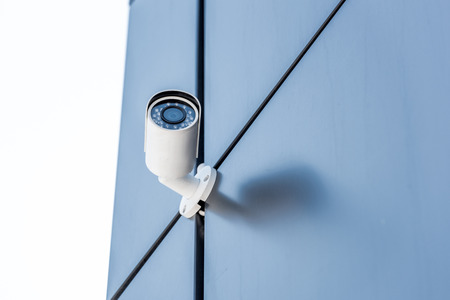 security camera on blue wall of office building, security system concept