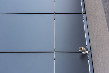 camera on wall of office building, security system concept