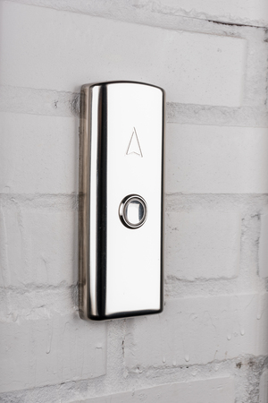 elevator button up direction on white wall Stock Photo - 84074267