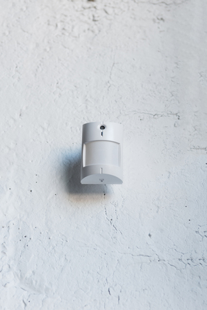 one white motion sensor on white wall