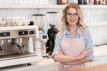 コーヒー マシンに近い作業中にバリスタ立っているを笑顔