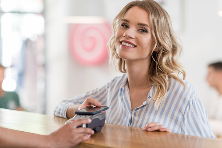 cardkey: beautiful smiling woman using smartphone for payment in cafe