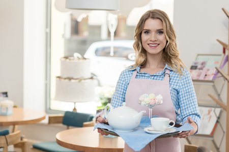 blonde waitress in apron holding tray with tea and cookies at cafe