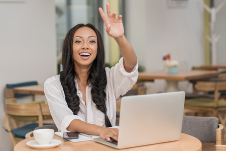 beautiful smiling african american businesswoman using laptop while sitting at cafe
