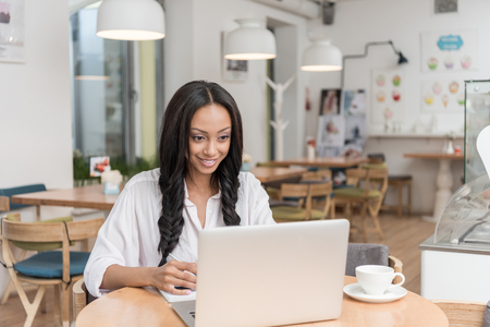 attractive african american smiling businesswoman working on laptop while sitting at cafe