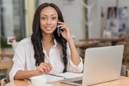 beautiful african american businesswoman talking on smartphone while sitting near laptop at cafe Stock Photo