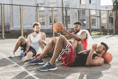 men resting after basketball game on court Stock Photo