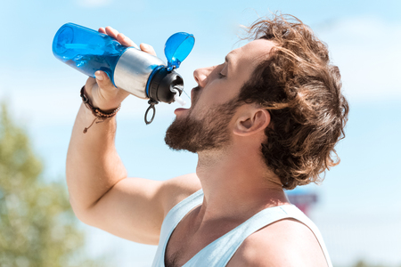 man drinkwater uit de sportieve waterfles Stockfoto