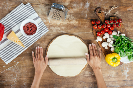 female hands rolling pizza dough with pin on table