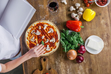 table top: woman holding blank cookbook while preparing pizza at kitchen Stock Photo