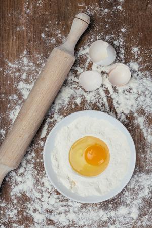 rauw ei met bloem, deegroller en de eierschaal op houten tafel