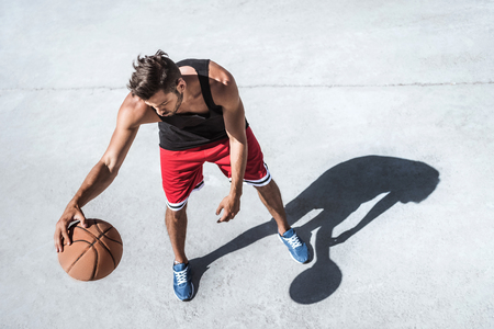handsome basketball player training on court alone
