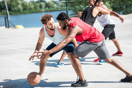 young multicultural men playing basketball on court Stok Fotoğraf
