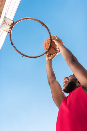 african american basketball player throwing ball into basket