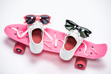 sneakers with sunglasses standing on pink skateboard
