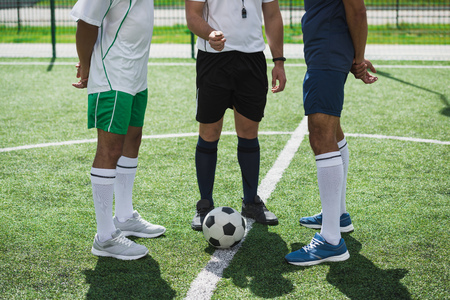 referee and soccer players on soccer pitch starting game