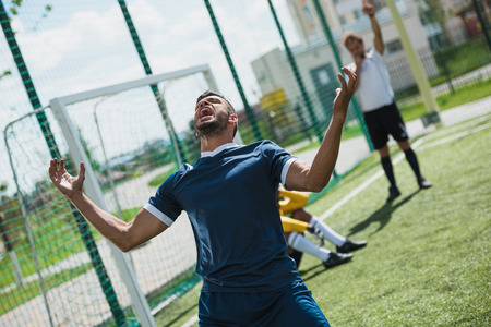 upset soccer player on soccer pitch during game Stock Photo