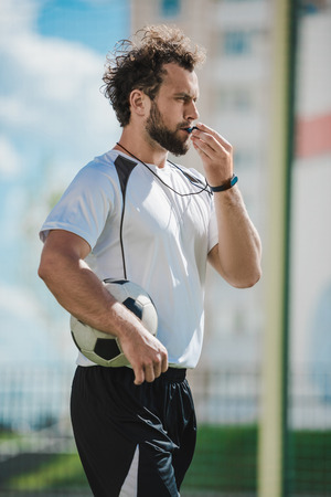 soccer referee whistling in whistle on soccer pitch during game Foto de archivo