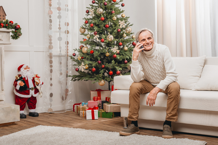 クリスマスに電話で話している男性 写真素材