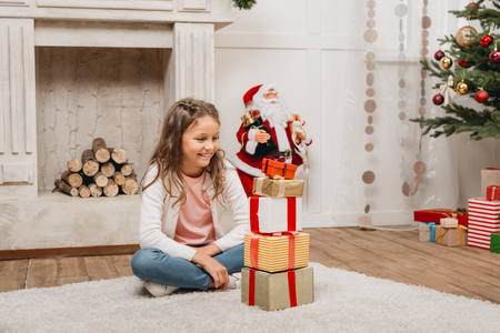 girl with stack of christmas gifts