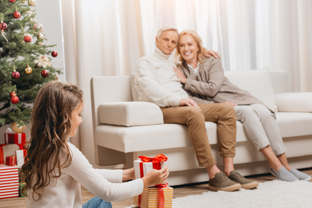 grandparents and granddaughter with gift boxes