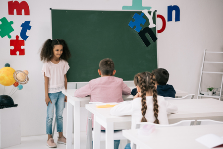 african american schoolgirl standing near chalkboard and looking at classmates sitting at desks