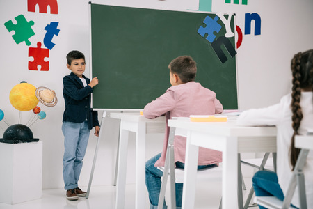 Schoolboy standing at chalkboard and looking at classmates sitting
